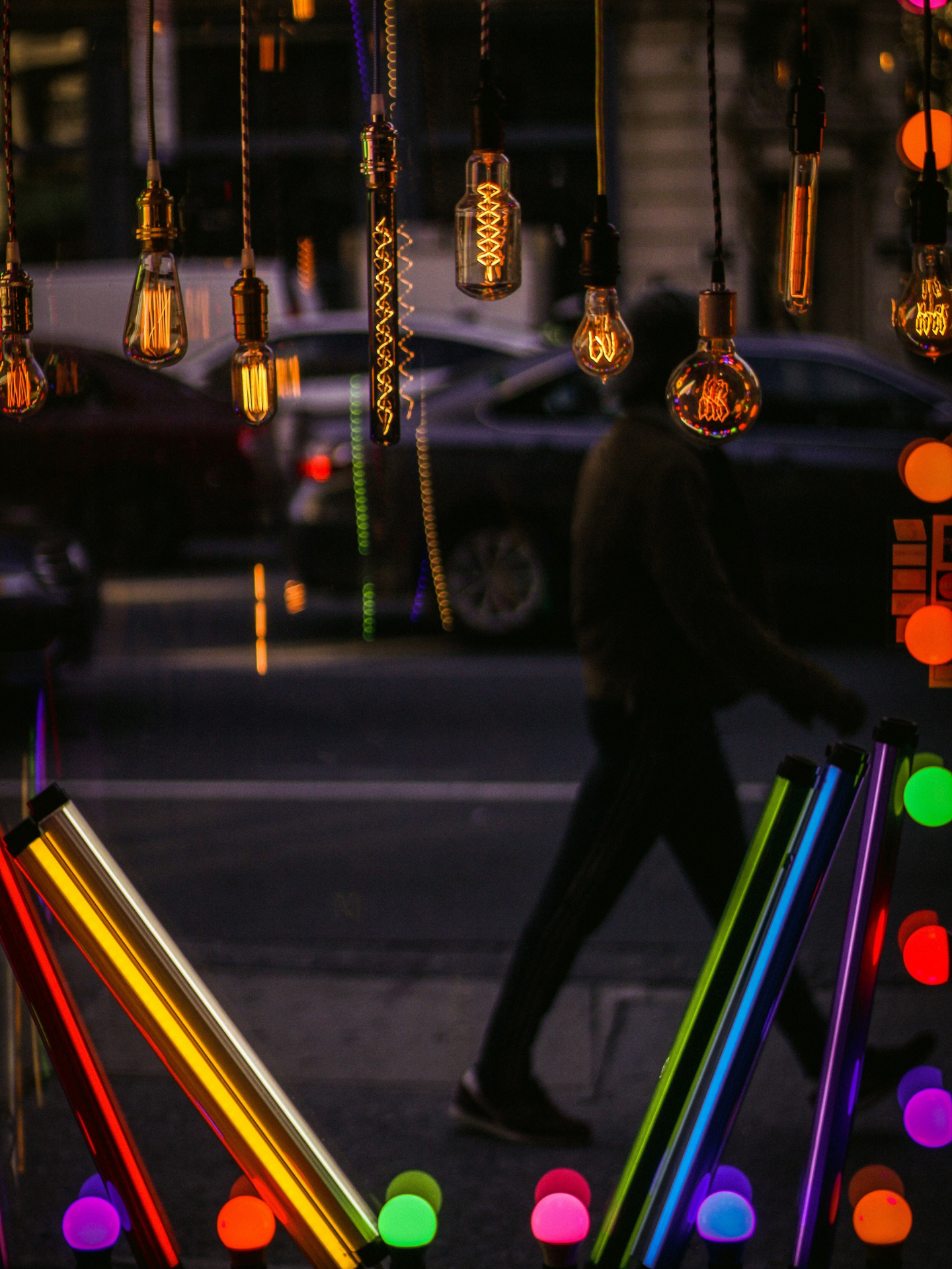 Man walking past colourful lighting shop display