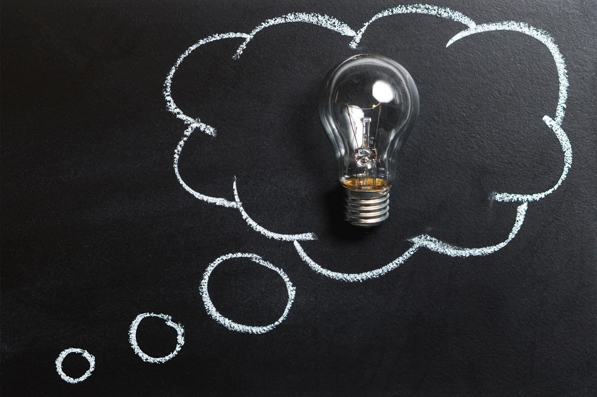Light bulb on blackboard background surrounded by an idea bubble