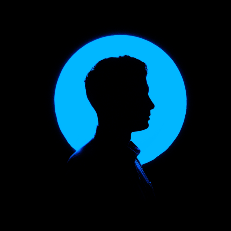 Male silhouette in front of blue light circle